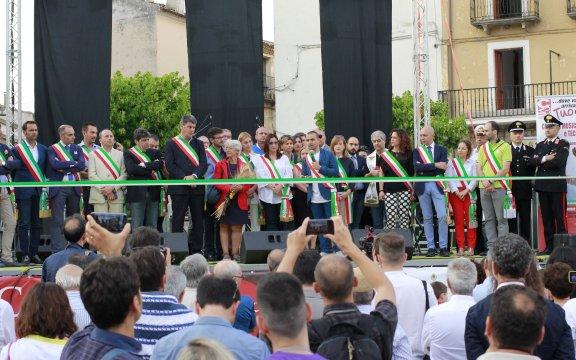 Uno scorcio sulla folla, si apre su un palco con sopra diversi Sindaci con fasce tricolori, in un momento inaugurale della Festa dei Borghi Autentici 2017